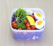 stock photo of lunch box  - Mix vegetable salad and boil eggs in plastic lunch box - JPG