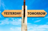 image of opposites  - Wooden signpost with two opposite arrows over clear blue sky Yesterday versus Tomorrow messages - JPG