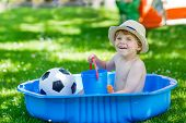 picture of kiddie  - Little toddler boy having fun with splashing water in summer garden pool - JPG
