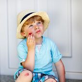 image of strawberry blonde  - Funny little kid boy eating fresh organic strawberries in domestic garden on warm summer sunny day - JPG