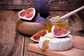 stock photo of meals wheels  - Camembert cheese with honey figs and honey dipper on a wooden board - JPG