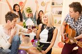 picture of court room  - A young guy is courting the pretty girl at home party while their friend plays acoustic guitar and in the background the rest of society with arms raised celebrated their relationship - JPG