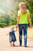 image of children walking  - mother of the child is a girl holding the hand of the road - JPG
