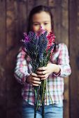 stock photo of wildflowers  - Little girl holding wildflowers in hands - JPG