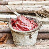 stock photo of grease  - Close up dirty grease and wooden paddle in old bucket on heap of lumber - JPG