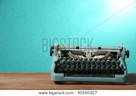 Old retro typewriter on table on green background