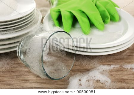 Dishes in foam with gloves on table close up