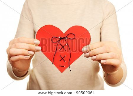 Woman holding stitched heart close up