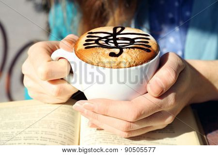 Hands holding cup of cappuccino with treble clef on foam