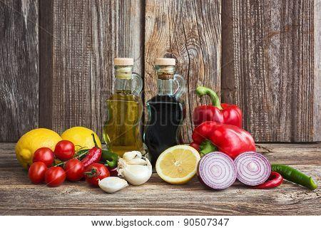 Olive Oil, Balsamic Vineger And Vegetables On Wooden Background