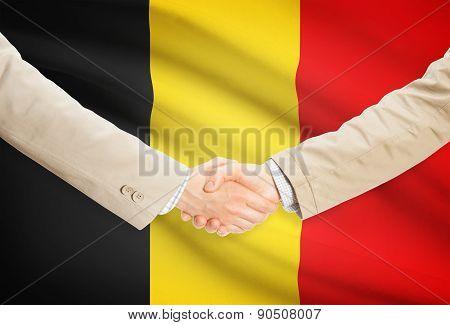 Businessmen Handshake With Flag On Background - Belgium