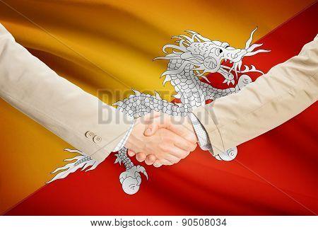 Businessmen Handshake With Flag On Background - Bhutan