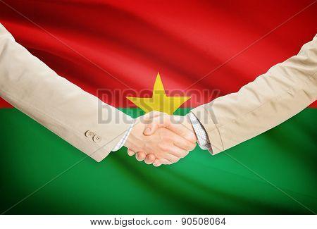 Businessmen Handshake With Flag On Background - Burkina Faso