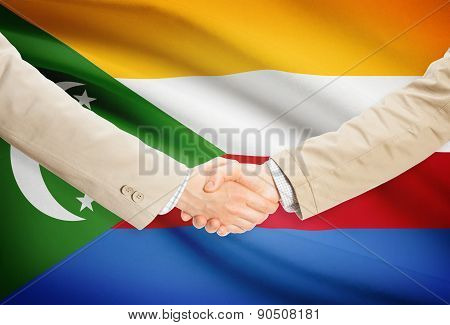 Businessmen Handshake With Flag On Background - Comoros