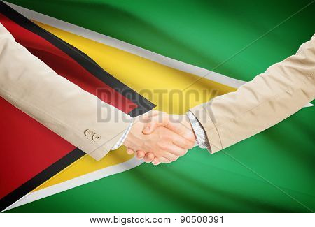 Businessmen Handshake With Flag On Background - Guyana