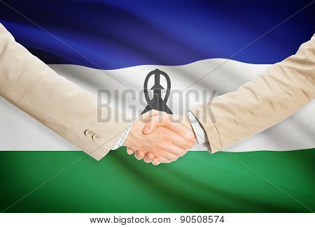 Businessmen Handshake With Flag On Background - Lesotho