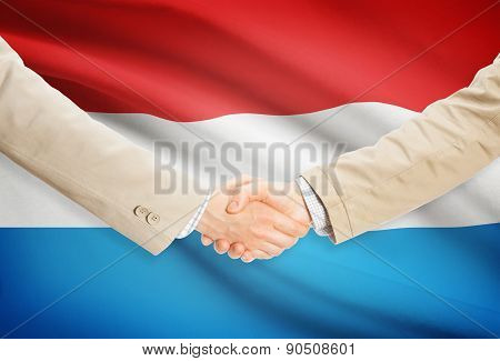 Businessmen Handshake With Flag On Background - Luxembourg