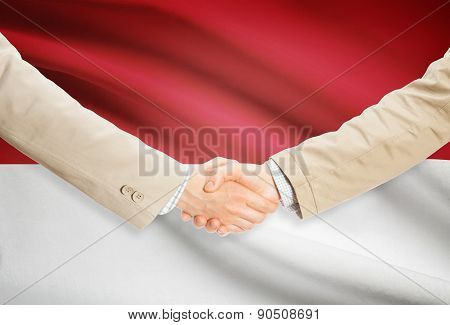 Businessmen Handshake With Flag On Background - Monaco