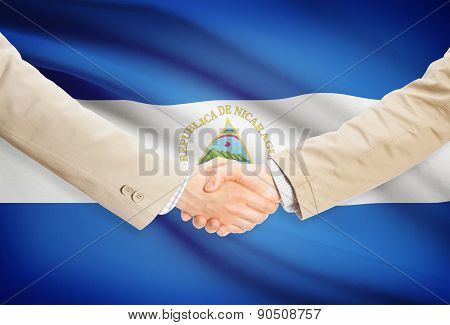 Businessmen Handshake With Flag On Background - Nicaragua