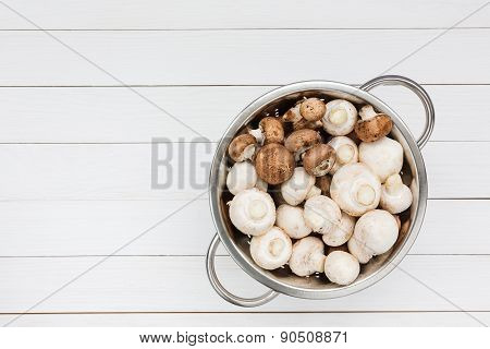 Fresh Mushrooms In Rustic Colander On White Wooden Table. Top View
