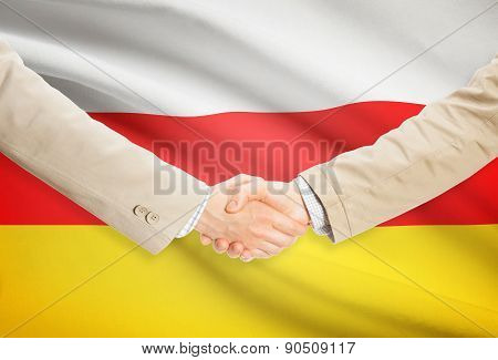 Businessmen Handshake With Flag On Background - South Ossetia