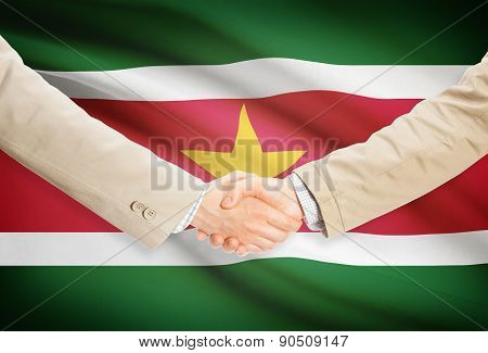 Businessmen Handshake With Flag On Background - Surinam