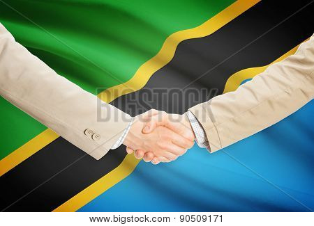 Businessmen Handshake With Flag On Background - Tanzania