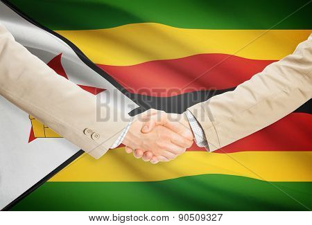 Businessmen Handshake With Flag On Background - Zimbabwe