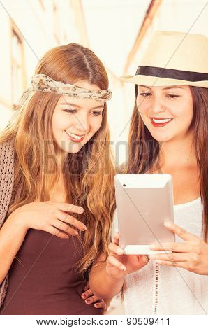 Beautiful young trendy girls using tablet