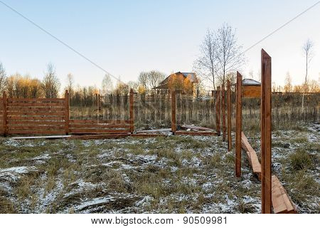 Unfinished Brown Wooden Fence On The Snowy Grass