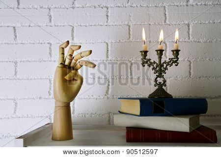 Bookshelf with books and candlestick on brick wall background