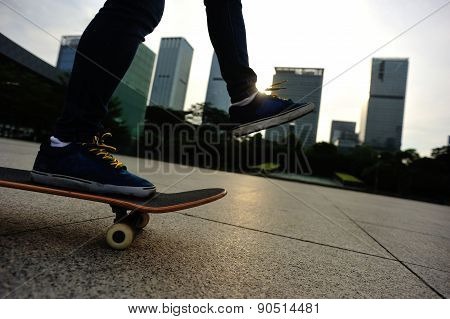 woman skateboarder legs riding on skateboard at sunrise city