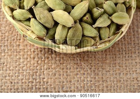 Green Cardamom pods in bamboo basket on sack cloth