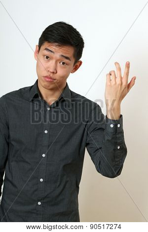 Frustrated young Asian man gesturing with his hand.