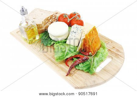 soft feta cheese with aged delicatessen cheeses on cutting wooden plate with tomatoes bread and olive oil isolated over white background