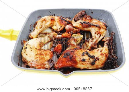 grilled chicken legs with tomatoes and thyme cooked on yellow ceramic pan isolated on white background