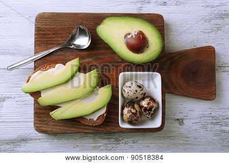 Slice of rye bread with sliced avocado and boiled quail eggson color wooden background