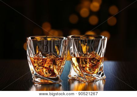Glasses of whiskey on bar background