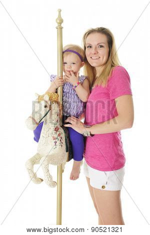 A happy mom standing by her adorable 2-year-old sitting on a carousel horse.  On a white background.