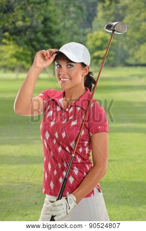 Portrait of beautiful young golfer tipping cap on golf course