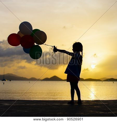 Silhouette of adorable happy little girl with bunch of balloons on sea coast at sunset