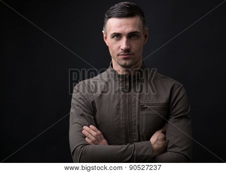 Portrait of a happy man standing with arms folded over black background and looking at camera