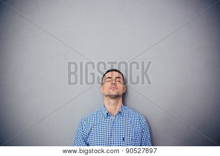 Portrait of a serious man with closed eyes leaning on the gray wall