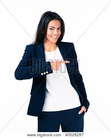 Portrait of a cheerful young businesswoman pointing finger away. Standing over white background. Looking at camera