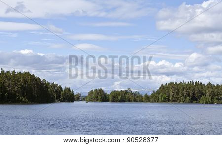 Lake, forests and mountains in the background.
