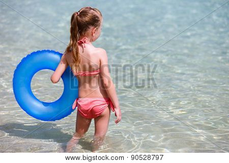 Little girl on vacation with blue inflatable ring in a shallow water on tropical vacation