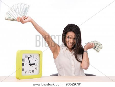 Happy young businesswoman sitting at the table with money over white background and looking at camera