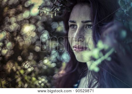 Feeling blue, melancholy young girl in a forest with sad gesture