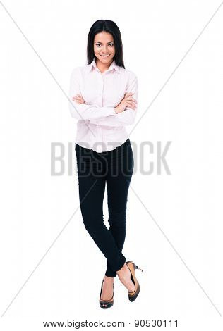 Full length portrait of a happy businesswoman standing with arms folded over white background and looking at camera