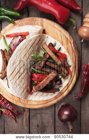 Fajitas, mexican beef stripes with grilled vegetable in tortilla wraps
